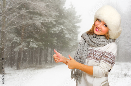 Young girl shows ok gesture at snowy forest