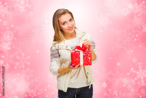 Young smiling girl with gift box on winter background
