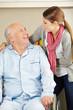 Senior im Rollstuhl lächelt Pflegehilfe an