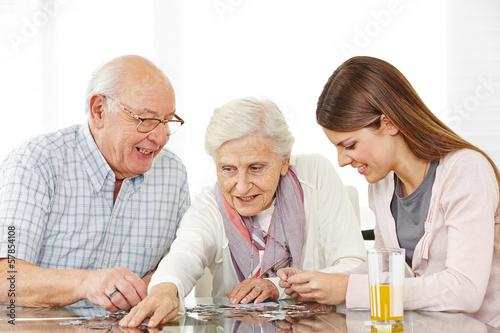 Zwei Senioren spielen ein Puzzle mit Enkelin