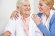 Frau umarmt Seniorin im Seniorenheim