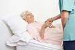 Seniorin liegt in Hospiz im Bett
