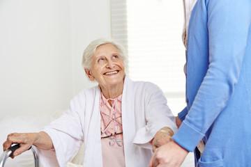 Krankenpflegerin hilft Seniorin beim Aufstehen