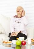 Lachende Seniorin telefoniert mit Smartphone