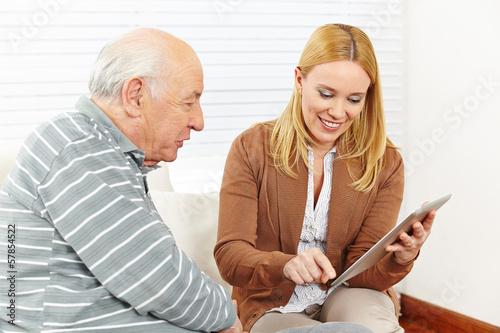 Tochter zeigt Senior Tablet Computer