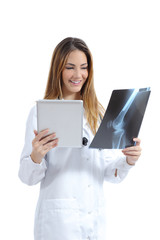 Female doctor comparing a tablet image with a radiography