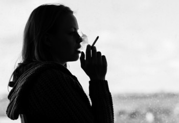 Silhouette of woman smoking cigarette