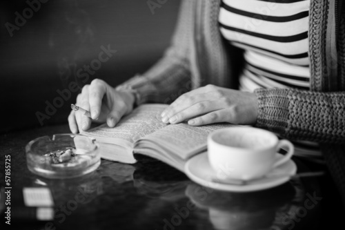Woman reading a book and smoking