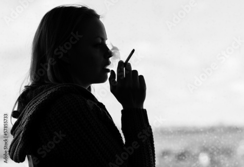 Silhouette of woman smoking cigarette