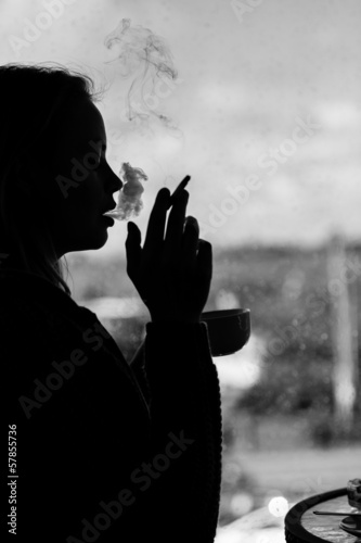 Silhouette of an attractive woman smoking cigarette