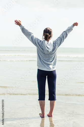 Woman opening her arms in front of the sea