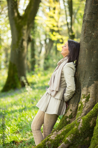 Woman leaning on a tree
