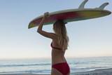 Fit blonde holding her surfboard on her head