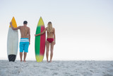 Cute attractive couple holding their surfboards