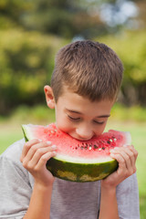 Cute boy holding and eating watermelon