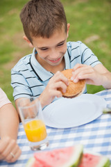 Young boy eating burger with his family