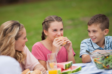 Young girl eating burger while mother and brother smiling at her