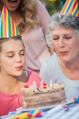 Close up of young girl and her grandmother blowing candles