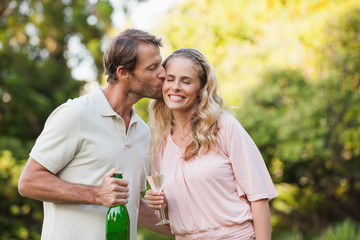 Man kissing his wife while holding champagne bottle