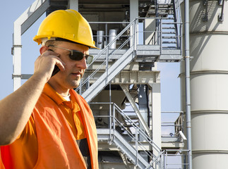 worker with helmet and sunglasses talking on mobile phone