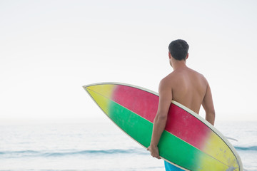 Pensive man holding his surfboard while looking at the sea