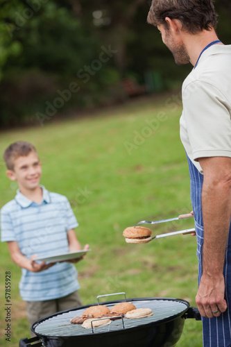 Father having barbecue giving burger to his son