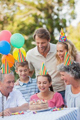 Cheerful family wearing party hat while celebrating birthday