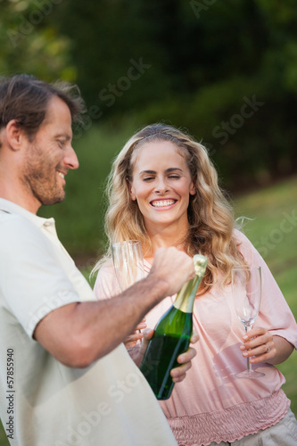 Happy couple opening champagne bottle