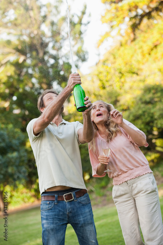 Young man opening champagne bottle with his wife