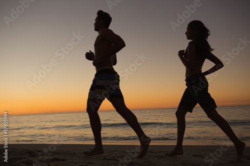 Sporty couple running together on the beach