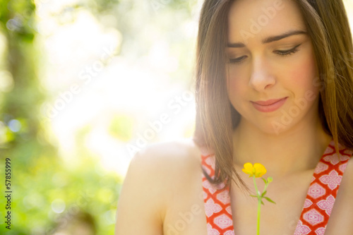 Brunette beauty looking at yellow flower