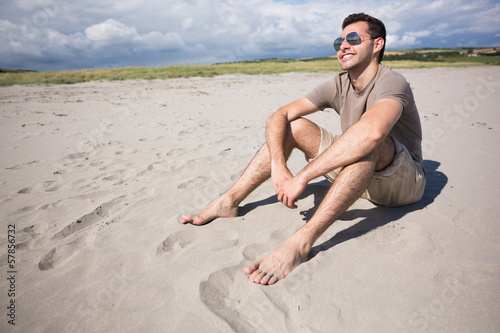Attractive smiling man sitting and enjoying the sun