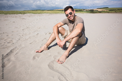 Attractive cheerful man sitting and enjoying the sun