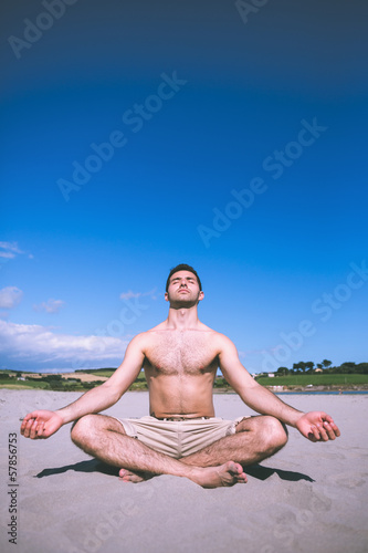 Attractive calm man relaxing topless with legs crossed
