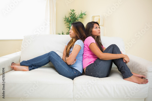 Two angry sisters sitting on a sofa
