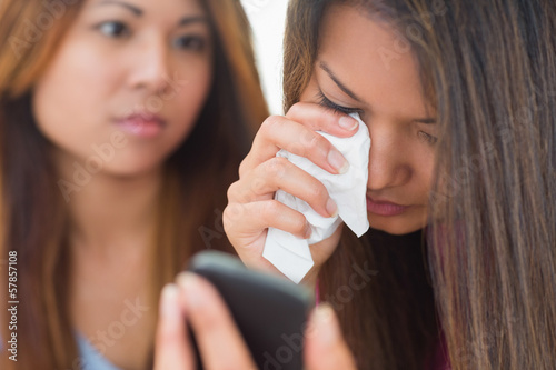Crying woman looking at phone being comforted by her sister