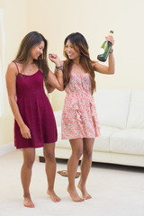 Two tipsy women dancing and drinking bottles of champagne