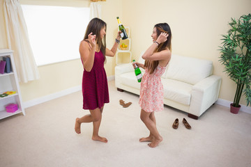 Two women dancing and drinking bottles of champagne