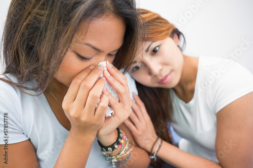 Sad beautiful woman crying while being consoled by her sister
