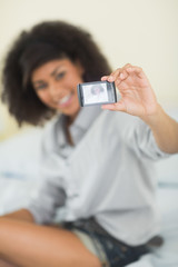 Picture of phone taking a picture of smiling brunette