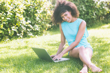 Gorgeous smiling brunette sitting on grass using laptop