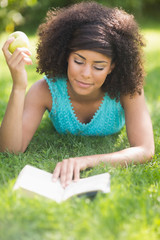 Gorgeous content brunette reading book holding apple