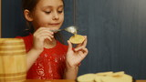 Girl puts honey on the spoon cookies
