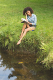 Gorgeous peaceful brunette sitting by the water reading book