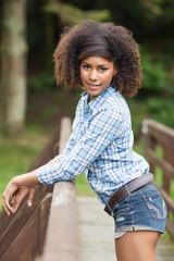 Gorgeous posing brunette leaning against bridge