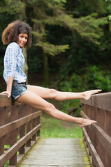 Gorgeous smiling brunette sitting on bridge