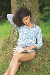 Gorgeous peaceful brunette leaning against tree reading