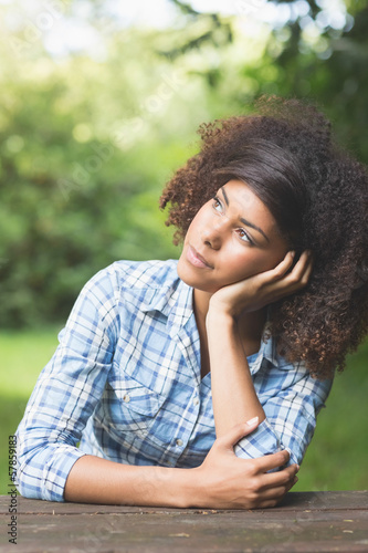 Gorgeous pensive brunette sitting at picnic table