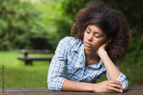Gorgeous day dreaming brunette sitting at picnic table
