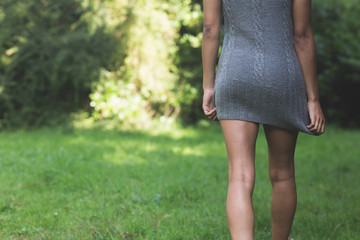 Rear view of lower body of model walking on grass pulling down dress